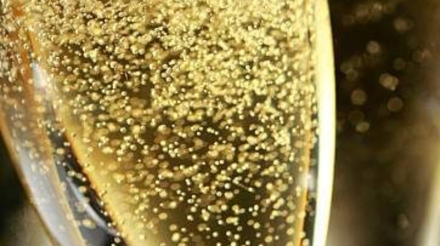 Close up of the bubbles in a freshly poured glasses of champagne.  The glasses are in front of a black background that allow for ample copy space.  Image can be flipped horizontal to accommodate  alternative composition needs. Shot with a very shallow depth of field.